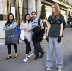 Modelo testa o sutiã acima da roupa nas ruas